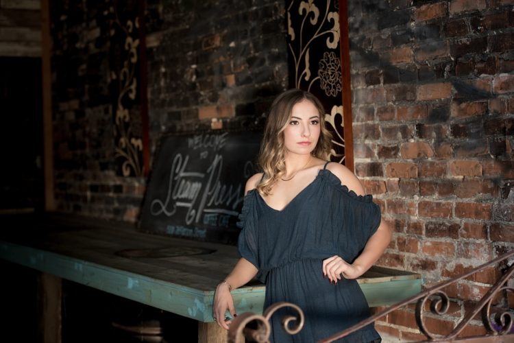 Gorgeous lighting for senior session in front of charred brick wall